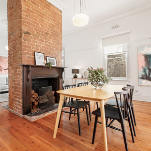 Contemporary open plan dining in Melbourne with white walls, medium hardwood floors, a standard fireplace, a brick fireplace surround and brown floor.