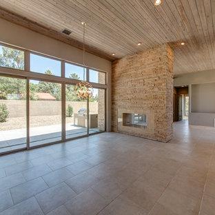 Idee per una grande sala da pranzo aperta verso il soggiorno contemporanea con pareti beige, pavimento con piastrelle in ceramica, camino bifacciale, cornice del camino in pietra e pavimento beige