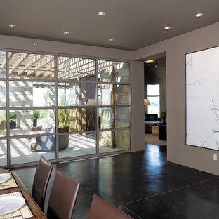 Trendy concrete floor and black floor dining room photo in Seattle