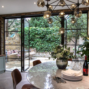 Inspiration for a contemporary open plan dining room in London with light hardwood flooring.