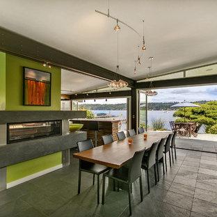 シアトルのモダンスタイルのおしゃれなダイニングキッチン (緑の壁、スレートの床、両方向型暖炉) の写真