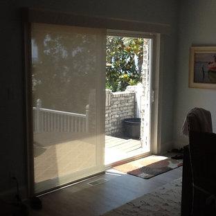 Immagine di una sala da pranzo aperta verso il soggiorno costiera di medie dimensioni con pareti grigie, pavimento in legno massello medio, nessun camino e pavimento marrone