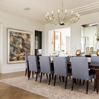 Example of a large transitional medium tone wood floor and brown floor enclosed dining room design in Dallas with white walls and no fireplace