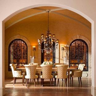 Cette photo montre une salle à manger méditerranéenne avec un mur beige et un sol en bois brun.