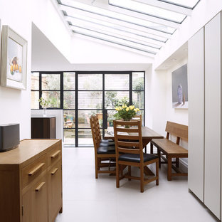 Design ideas for a contemporary open plan dining room in London with white walls and white floors.