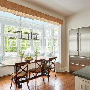 Cette photo montre une grande salle à manger ouverte sur la cuisine chic avec un sol en bois brun.