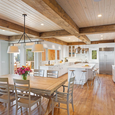 Example of a large beach style medium tone wood floor kitchen/dining room combo design in New York with gray walls and no fireplace