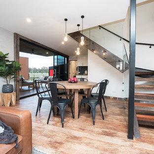 Immagine di una piccola sala da pranzo aperta verso il soggiorno contemporanea con pareti bianche e pavimento in vinile