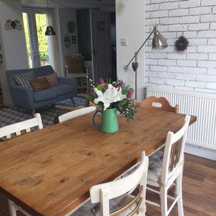 Foto di una sala da pranzo aperta verso il soggiorno country di medie dimensioni con pareti bianche, pavimento in laminato, stufa a legna e cornice del camino piastrellata