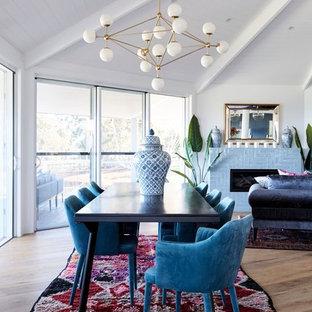 Réalisation d'une salle à manger ouverte sur le salon avec un mur blanc, un sol en bois clair, une cheminée standard et un manteau de cheminée en carrelage.