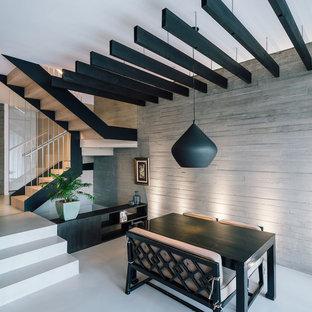 Modelo de comedor actual, de tamaño medio, abierto, con paredes grises, suelo de cemento y suelo gris
