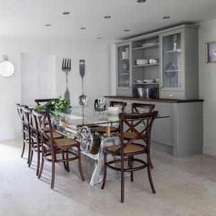 Immagine di una sala da pranzo aperta verso la cucina chic di medie dimensioni con pavimento in pietra calcarea, pavimento grigio e pareti bianche