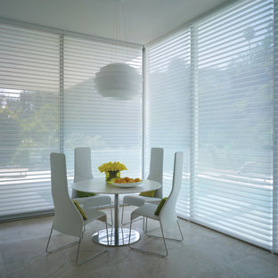 Idee per una sala da pranzo aperta verso la cucina minimalista di medie dimensioni con pareti bianche, pavimento in pietra calcarea e nessun camino