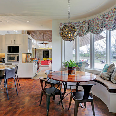 Large trendy medium tone wood floor and brown floor kitchen/dining room combo photo in Houston with white walls and no fireplace