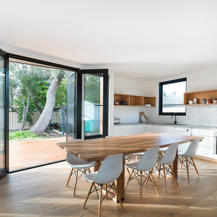 Inspiration for a contemporary kitchen/dining combo in Melbourne with white walls and light hardwood floors.