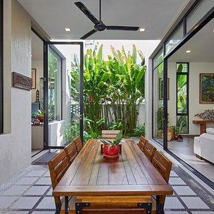 Idées déco pour une salle à manger exotique avec un mur blanc et béton au sol.