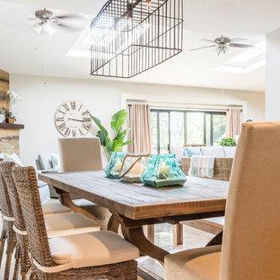 Esempio di una sala da pranzo aperta verso il soggiorno stile marino di medie dimensioni con pareti bianche, pavimento con piastrelle in ceramica, camino classico, cornice del camino in legno e pavimento beige