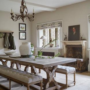 Ispirazione per una sala da pranzo chic di medie dimensioni e chiusa con pareti beige, pavimento beige, camino classico e cornice del camino in mattoni