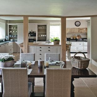 Modelo de comedor de cocina campestre, grande, con suelo de piedra caliza, paredes blancas, chimenea tradicional y marco de chimenea de piedra