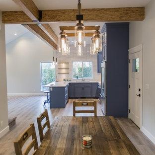 Foto di una sala da pranzo aperta verso la cucina minimalista di medie dimensioni con pareti bianche, pavimento in laminato e pavimento marrone