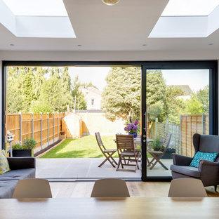 Foto di una grande sala da pranzo aperta verso il soggiorno contemporanea con pareti gialle, pavimento in legno massello medio e nessun camino