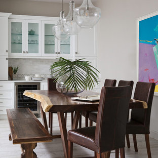 Foto di una grande sala da pranzo aperta verso il soggiorno tradizionale con pareti grigie, pavimento in gres porcellanato, camino bifacciale, cornice del camino piastrellata e pavimento bianco
