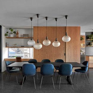 Modernes Esszimmer mit Betonboden, Eckkamin, Kaminsims aus Beton und schwarzem Boden in Melbourne