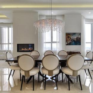 Imagen de comedor contemporáneo, de tamaño medio, con paredes blancas, suelo de mármol, chimenea tradicional, marco de chimenea de yeso y suelo blanco