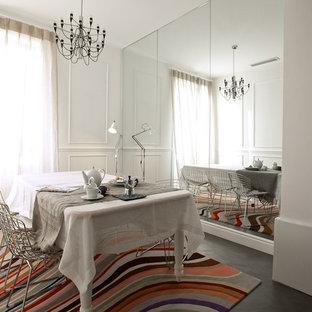 Modelo de comedor bohemio con paredes blancas y suelo de cemento
