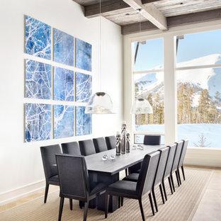 Cette image montre une salle à manger chalet avec un mur blanc, un sol en bois clair, un sol beige, un plafond en poutres apparentes et un plafond en bois.