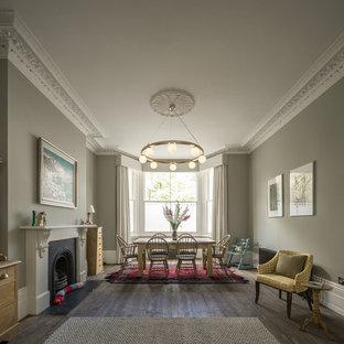 Идея дизайна: столовая в классическом стиле с серыми стенами, темным паркетным полом, стандартным камином и фасадом камина из металла