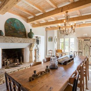 Réalisation d'une grande salle à manger méditerranéenne avec un mur blanc, un sol en carreau de terre cuite, une cheminée standard et un manteau de cheminée en pierre.