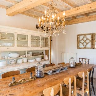 Réalisation d'une salle à manger méditerranéenne avec un mur blanc, aucune cheminée et un sol gris.