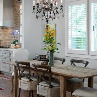 Esempio di una piccola sala da pranzo aperta verso il soggiorno tradizionale con pareti beige, pavimento in legno massello medio, camino classico, cornice del camino in mattoni e pavimento marrone