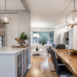 Immagine di una sala da pranzo aperta verso la cucina classica di medie dimensioni con pareti grigie, parquet chiaro, camino sospeso e pavimento beige