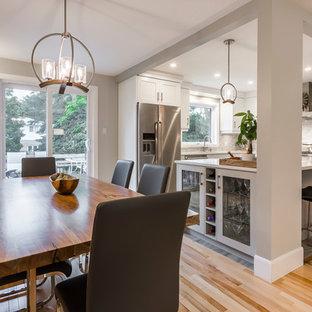 Esempio di una sala da pranzo aperta verso la cucina classica di medie dimensioni con parquet chiaro, camino sospeso e pavimento beige