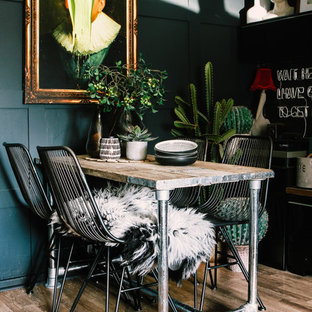 Design ideas for a bohemian dining room in Cardiff with black walls, medium hardwood flooring and brown floors.