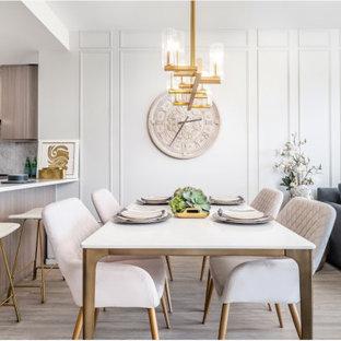 Immagine di una piccola sala da pranzo aperta verso la cucina eclettica con pareti grigie, pavimento in laminato e pavimento grigio