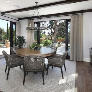 На фото: столовая в средиземноморском стиле с серыми стенами, темным паркетным полом и балками на потолке без камина