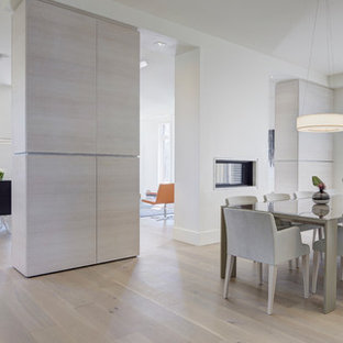 Foto di una grande sala da pranzo aperta verso il soggiorno scandinava con pareti bianche, pavimento in legno massello medio e pavimento giallo