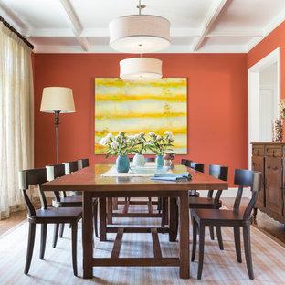 Réalisation d'une grande salle à manger tradition fermée avec un mur orange, un sol en bois brun et aucune cheminée.