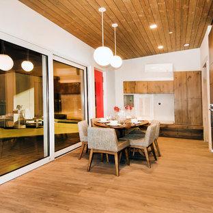 Modelo de comedor vintage, pequeño, abierto, con paredes blancas y suelo de madera en tonos medios