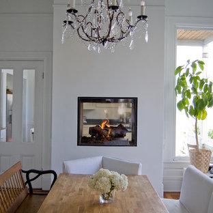 Diseño de comedor de cocina bohemio con paredes blancas, suelo de madera clara y chimenea de doble cara