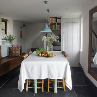 Example of a small cottage dining room design in Cornwall with white walls and no fireplace