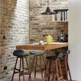 Photo of an industrial dining room in London with medium hardwood flooring.