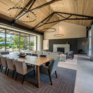 Idées déco pour une très grand salle à manger ouverte sur le salon campagne avec un mur beige, béton au sol, un sol gris et un plafond voûté.