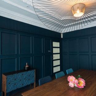 ロンドンのミッドセンチュリースタイルのおしゃれな独立型ダイニング (青い壁、濃色無垢フローリング、標準型暖炉、漆喰の暖炉まわり) の写真