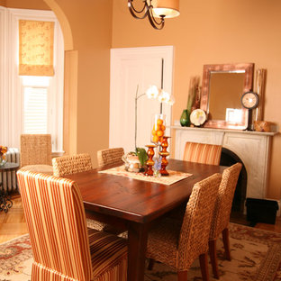 Dining room - traditional medium tone wood floor dining room idea in Boston with orange walls and a standard fireplace