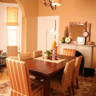 Immagine di una sala da pranzo classica con pareti arancioni, pavimento in legno massello medio e camino classico