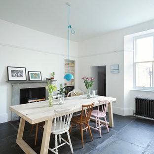 Пример оригинального дизайна интерьера: большая кухня-столовая в скандинавском стиле с белыми стенами, полом из сланца, печью-буржуйкой, фасадом камина из камня и черным полом